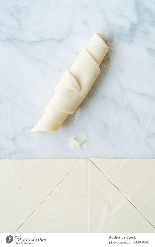 Teighörnchen und geschnittener Teig auf dem Tisch süß Croissant Teigwaren rollierend Mehl Vorbereitung aufgeschnitten Bäckerei selbstgemacht kulinarisch