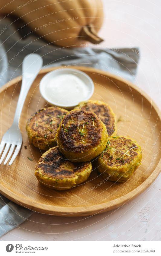 Köstliche Gemüseschnitzel mit saurer Sahne auf dem Tisch Kotelett Kürbis traditionell gebraten golden Küche Speise lecker Feinschmecker Teller Mahlzeit