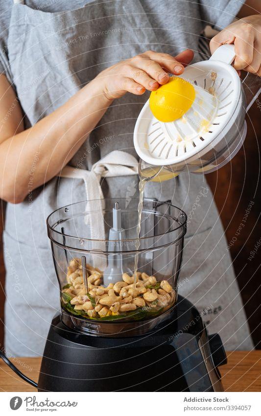 Erntehelferin gibt Zitronensaft in den Mixer Frau Mischer Koch Saft verschütten Entsafter Cashewnuss Küche Veganer Gesundheit Speise Küchengeräte Vorrichtung