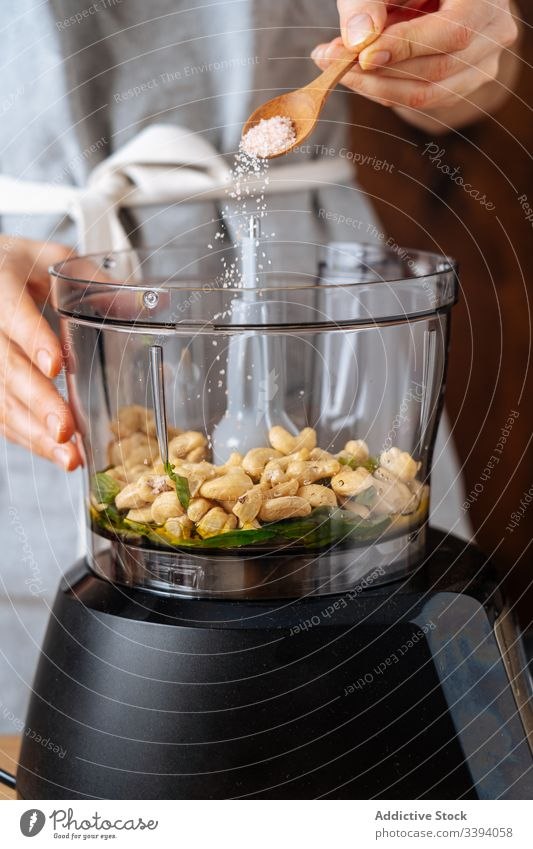 Erntehelferin gibt Salz in den Mixer Frau Mischer Koch verschütten Entsafter Cashewnuss Küche Veganer Gesundheit Speise Küchengeräte Vorrichtung hinzufügen