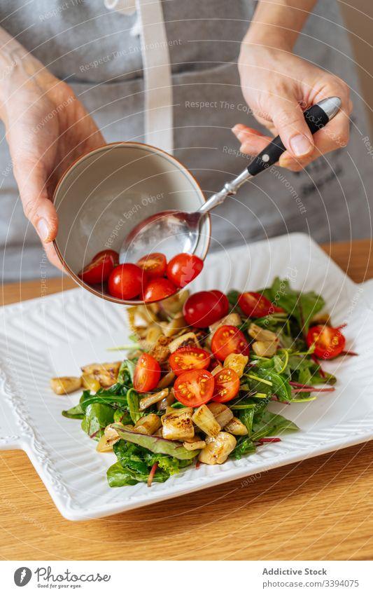 Frau legt Tomaten auf den Salat Lebensmittel Essen zubereiten Salatbeilage Kirsche Rezept Gemüse Bestandteil Küche Gesundheit Mahlzeit Hausfrau Abendessen