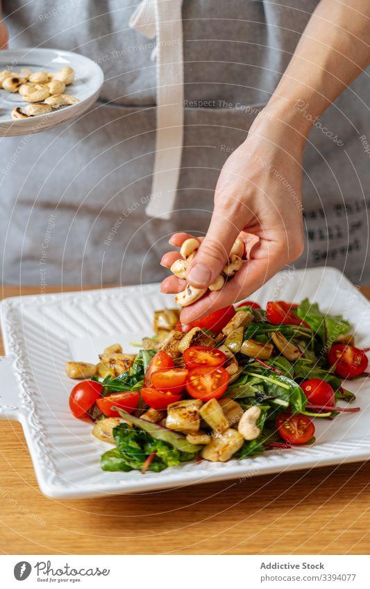 Frau garniert Salat mit Nüssen Lebensmittel Essen zubereiten Salatbeilage Rezept Cashewnuss Muttern Gemüse Bestandteil Garnierung Küche Gesundheit Mahlzeit