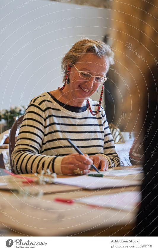Künstlerin zeichnet mit Bleistift im Kunstatelier Frau Beschriftung Handschrift zeichnen Konzentration kreativ Fokus Lifestyle lernen Job sitzen Skizze