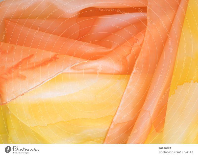 Nahaufnahme eines handfarbenen orange-gelben Seidenschals pongé Wasserfarbe Waldorf Acryl Aquarell Kunst künstlerisch Textil Gewebe Seidenmalerei Malerei