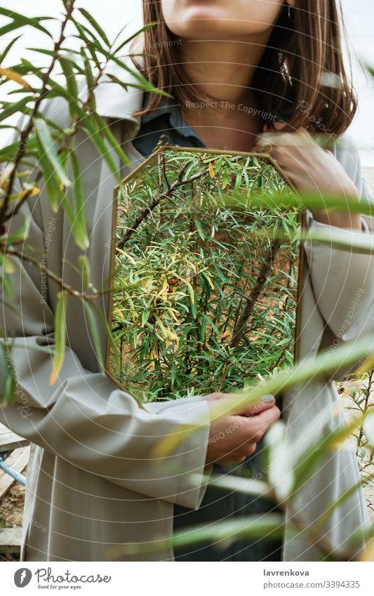 Nahaufnahme einer Frau, die einen Spiegel mit Sanddornbeeren hält, Spiegelung von Sträuchern, selektiver Fokus Graben Beteiligung Hände gesichtslos Baum