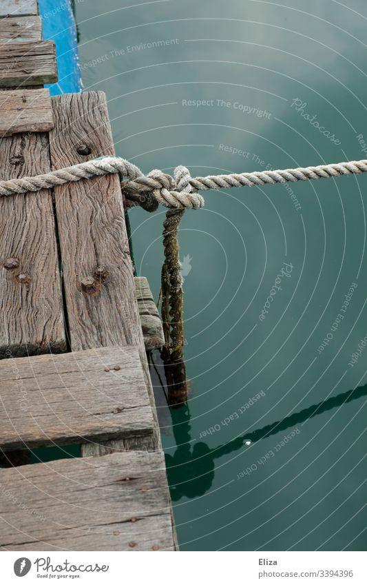 Ein Holzsteg mit einem Tau und einem Knoten über türkisem Wasser Holzssteg Steg verknotet Meer maritim fest vertaut festbinden festgebunden Seil Menschenleer