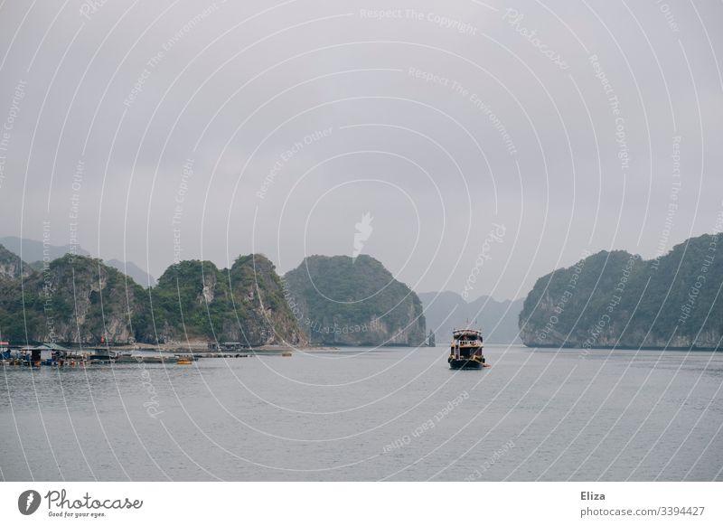Ein Ausflugsschiff in der Halong Bay in Vietnam; schöne Landschaft mit Kalksteinfelsen, die aus dem Meer ragen, bei nebligem Wetter Schiff Boot Sehenswürdigkeit