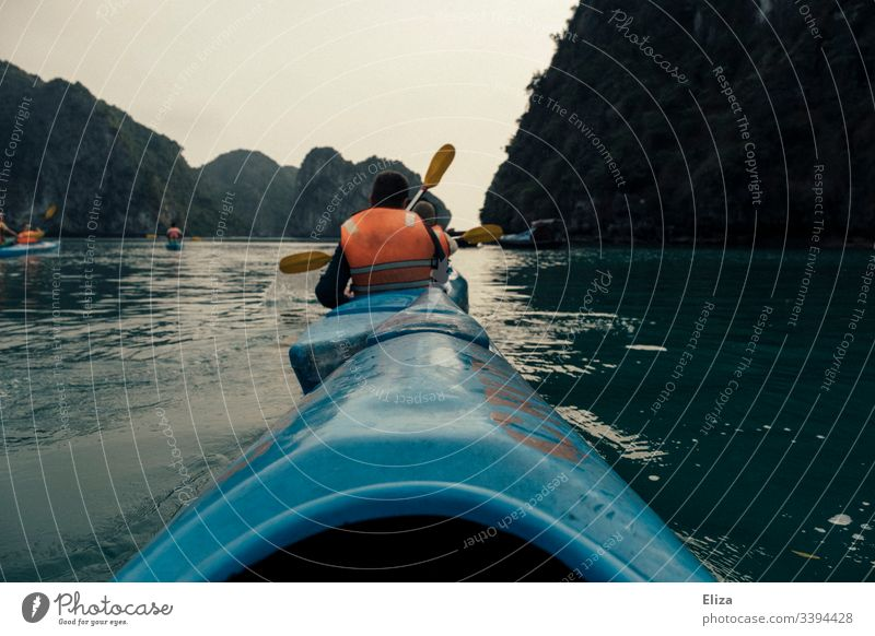 Kajafahrende Touristen in blauen Kajaks mit Orangen Schwimmwesten in der Halong Bay in Vietnam Meer Kajakfahren Wasser Aussicht Sport Abenteuer Felsen Natur