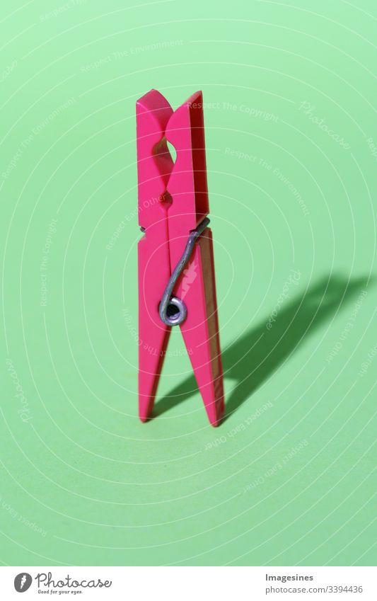 Wäscheklammer - rosa gefärbte Plastik Wäscheklammer auf grünem Hintergrund. Minimale Konzeptkunst. Abstraktion. Schatten. Farbige Wäscheklammer isoliert