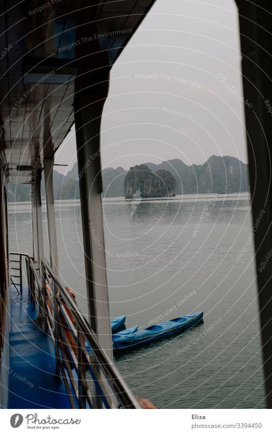 Aussicht von einem Ausflugsschiff, mit Reling und angebundenen Kajaks, in der Halong Bay in Vietnam; schöne Landschaft mit Kalksteinfelsen, die aus dem Meer ragen, bei nebligem Wetter