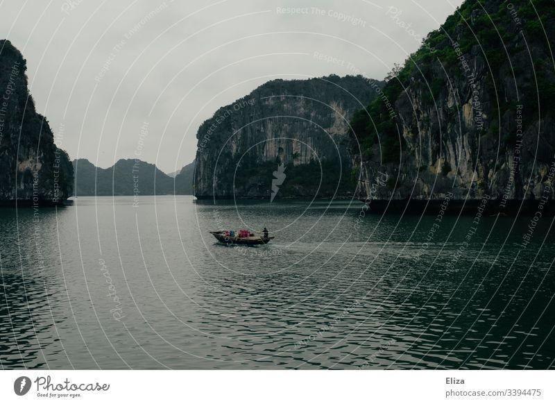 Ein Fischerboot auf dem Meer in der Halong Bay in Vietnam; schöne Landschaft mit Kalksteinfelsen, die aus dem Meer ragen, bei nebligem Wetter Sehenswürdigkeit