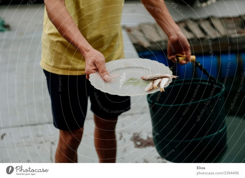 Ein Fischer hält einen Teller mit Fischen in der Hand Fischerei Fischzucht Futter mann halten verfüttern Wasser Fischereiwirtschaft dokumentarisch Vietnam