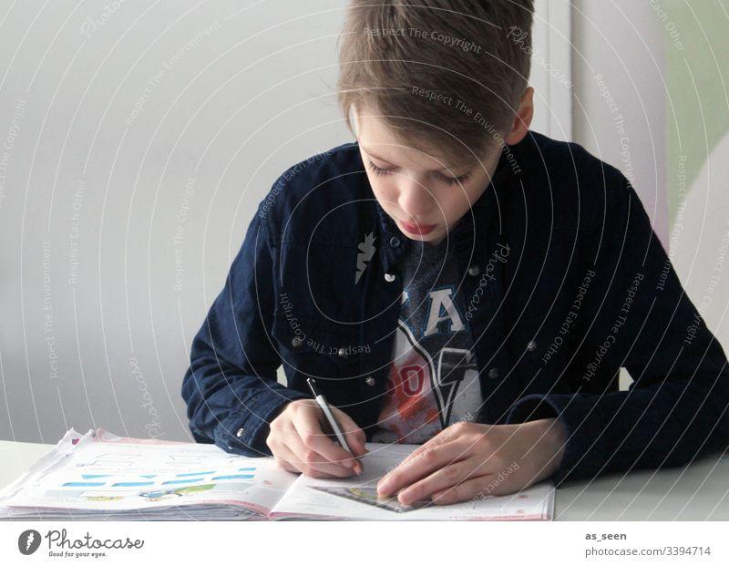 Junge macht Hausaufgaben blond hair Haare & Frisuren Stift Bleistift Gesicht Blick Porträt Blick nach unten schreiben schreibend Jugendliche konzentriert