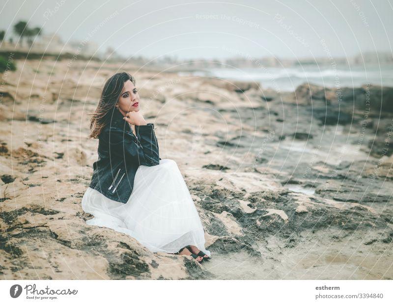 Nachdenkliche junge Frau am Strand sitzend Junge Frau schön elegant Eleganz träumen träumend Träume Kleid Mode Freiheit Spaß Glamour Selbstständigkeit Freude