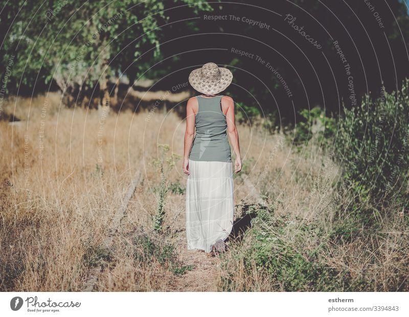 Rückansicht einer nachdenklichen jungen Frau auf dem Feld Junge Frau träumend Träume Freiheit Gras in der Liebe Landschaft Freizeit Lifestyle schön Einsamkeit