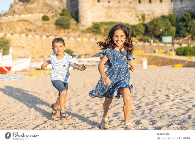 Zwei kleine Freunde laufen am Strand Aktion aktiv schön blau Jungen heiter Kind Kindheit Kinder bunt Konkurrenz Konzept niedlich Freundschaft Spaß lustig