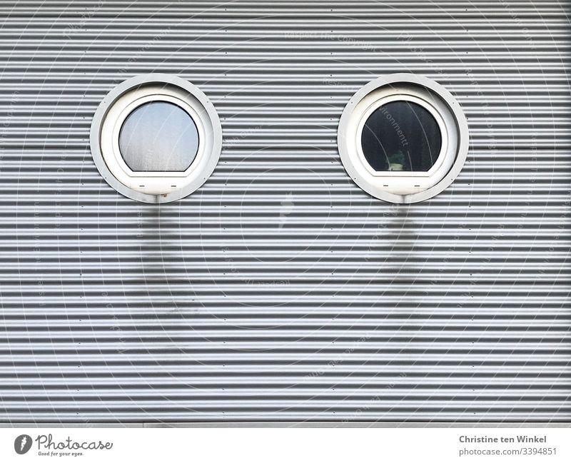 Zwei runde Fenster in einer verkleideten Hausfassade weiß Fassade Gebäudefassade schmutzig silber Fassadenverkleidung silberfarben grau trist Streifen Linien
