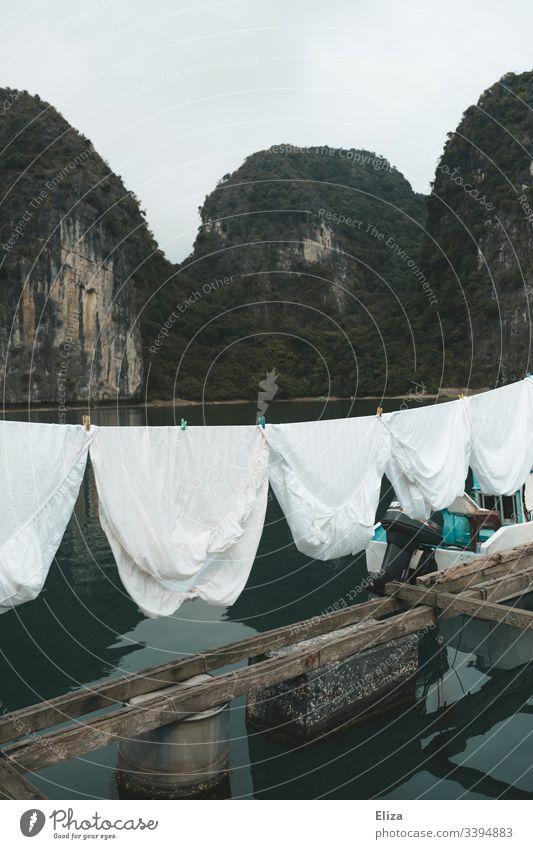 Weiße Wäsche auf einer Wäscheleine in einem schwimmenden Dorf in der Halong Bucht in Vietnam Bettlaken Floating Village schwimmendes Dorf Kalksteinfelsen