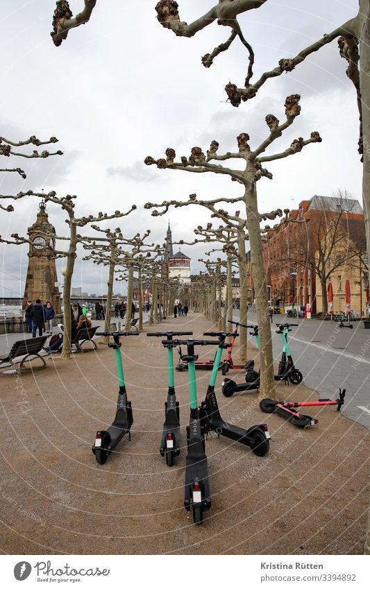 elektroroller am rathausufer in düsseldorf e-roller e-scooter leihroller elektroscooter pegeluhr schlossturm rheinufer rheinuferpromenade mobil mobilität