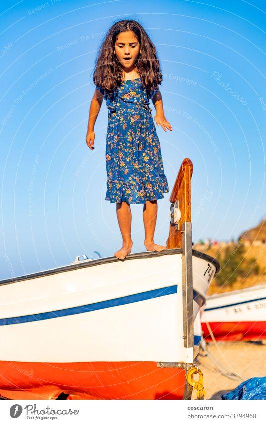 Kleines Kind, das aus einem Boot mit blauem Himmelshintergrund springt aktiv Air Hintergrund Strand schön Junge sorgenfrei heiter Kindheit Küste Küstenlinie