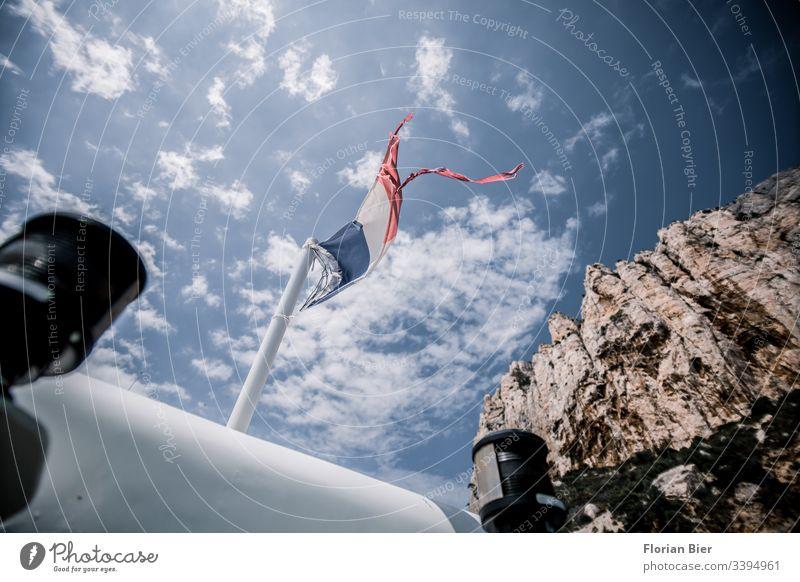 Französische Flagge im Wind auf einem Boot Frankreich Fahne Himmel Wolken Berge Klippe maritim Fahnenstange Sommer Sonne rot weiß blau Signallampe wehen
