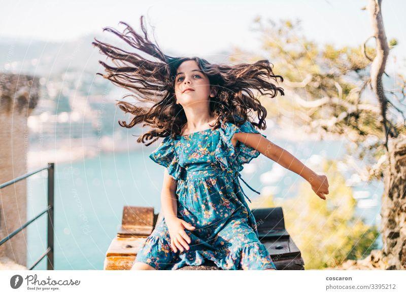 Lustiges kleines Mädchen, das sein langes Haar bewegt Aktivität bezaubernd die Arme weit geöffnet schön Schönheit Kaukasier schick Kind Kindheit Kleidung Küste