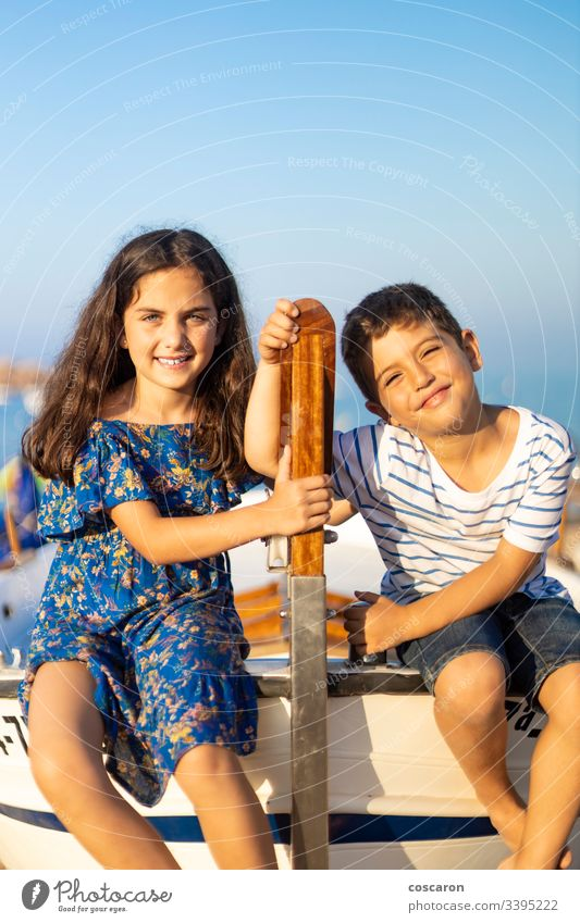 Porträt von zwei kleinen Kindern, die am Strand in ein Fischerboot geklettert sind Abenteuer blau Holzplatte Boot Junge Brüder Kapitän Kindheit Küste