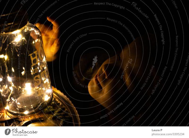Kleines Mädchen, das einen Krug mit Lichtern berührt wenig dunkel berühren Glas Stille Zauberei u. Magie Glanz glänzend Hand