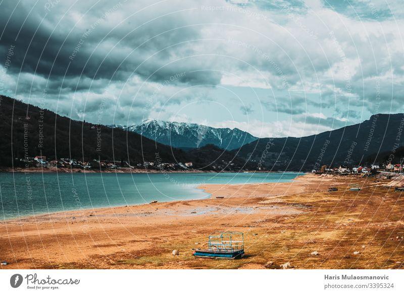 Wunderschöne Landschaftsansicht mit Blick auf die Gezeiten des Sees und die Schneegipfel der Berge in der Ferne Bahn Feld Hintergrund PKW Ladung Konstruktion