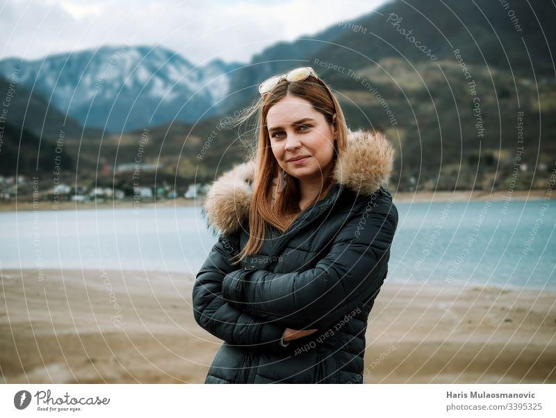 Junge schöne blonde Frau in der Natur, am Seeufer und auf dem Berggipfel im Hintergrund Erwachsener Abenteuer attraktiv Schönheit Kaukasier kalt Textfreiraum