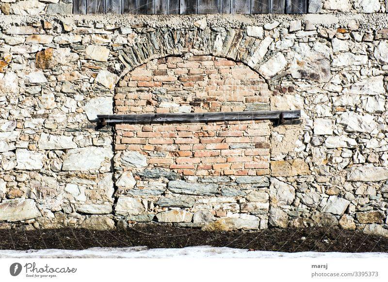 Eine Steinmauer mit einem zugemauerten Tor, das zusätzlich mit einem Balken gesichert ist. Fachmännisch gemauerter Torbogen. Mauer Türsicherung Farbfoto