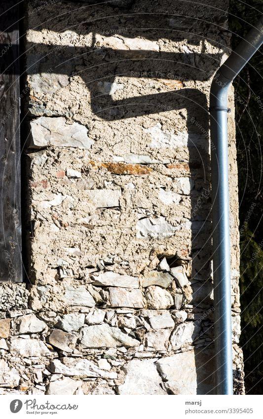 Schatten eines Regenrohrs auf einer Steinmauer Steinwand geschnallt gebeugt Fallrohr bügeln Steine Wand Haus Fassade Licht