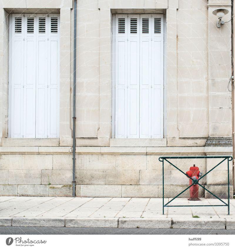 Hydrant hinter Gitter Pfeil Fenster Fensterladen Sprossenfenster Natursteinfassade Fassade Mauer Wand Jalousie Rollladen Depression Zentralperspektive Verlassen