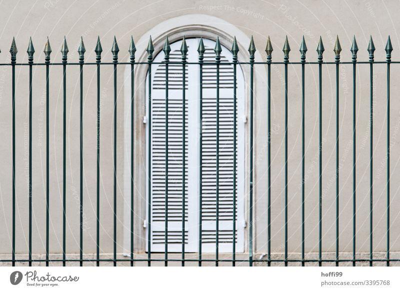 eleganter hoher Zaun vor Fenster mit geschlossenen Fensterläden Pfeil Fensterladen Sprossenfenster Natursteinfassade Fassade Mauer Wand Jalousie Rollladen