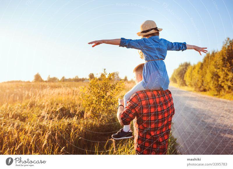 glückliche Vater und Tochter, die auf der Sommerwiese spazieren gehen, Spaß haben und spielen. Vatertag, Konzept der Vaterschaft. Bäuerliches Leben. Kind