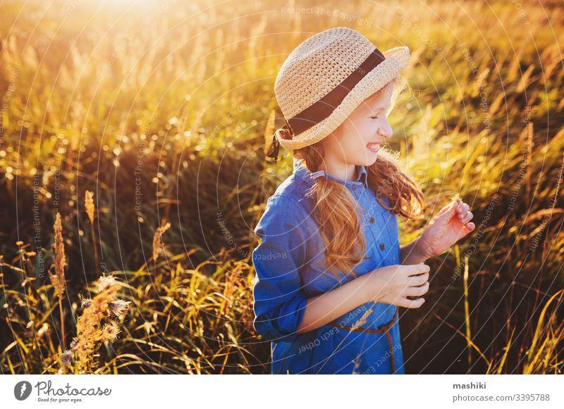 glückliches Mädchen in blauem Kleid und Stroh, das auf einer sonnigen Sommerwiese spazieren geht. Lifestyle-Aufnahme, ländliches Leben und Sommerreisekonzept