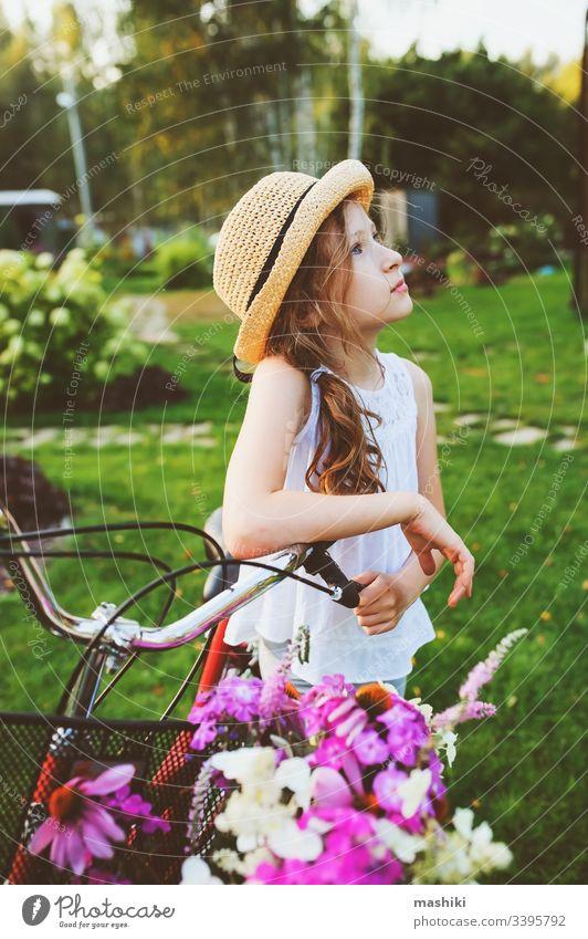 fröhliches Kind Mädchen mit Hut Fahrrad fahren mit Wildblumenstrauss, Sommerferienkonzept Buch Kindheit im Freien Natur Park Spaß Glück Lifestyle lesen Freizeit