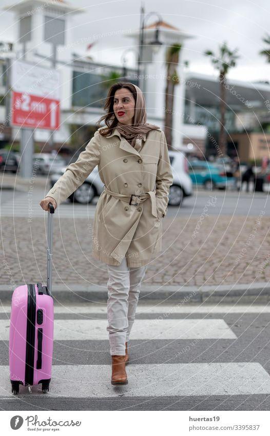 Attraktive arabische Frau mit Hidschab und Koffer Hijab attraktiv muslimisch muslimische Frau Handy Gepäck Reisen: islamisch Reisender Ausflug Fröhlichkeit