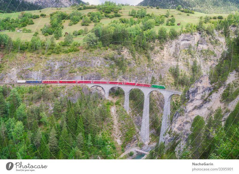 Roter Schnellzug fährt auf der berühmten Landwasser-Brücke in Filisur, dem Herzen der alpinen Berge in der Schweiz Zug landwasser Schweizer Natur Architektur