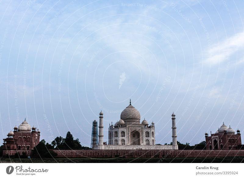 Das märchenhafte Taj Mahal mit seinen beiden Nebengebäuden. Fast so, als würden die beiden Nebengebäude aus Sandstein die wunderbare Königin, das Grabmal einer großen Liebe, wachen.  Eine Totale von der anderen Seite des heiligen Yamuna-Flusses