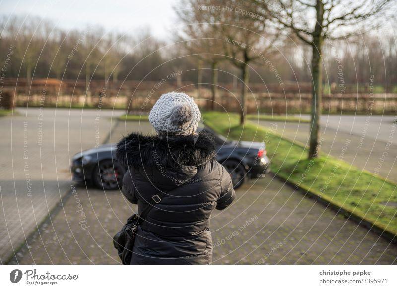 Frau in schwarzer Winterjacke und Mütze schaut auf schwarzen Roadster auf Parkplatz Jacke KFZ Tag parken roadster Sportwagen PKW Außenaufnahme Fahrzeug Cabrio