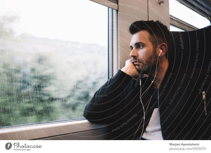 Junger Mann im Zug mit Kopfhörern 30s Erwachsener allein bärtig lässig Kaukasier Arbeitsweg Pendler Tag täglich Typ gutaussehend Reise Leben Lifestyle hören