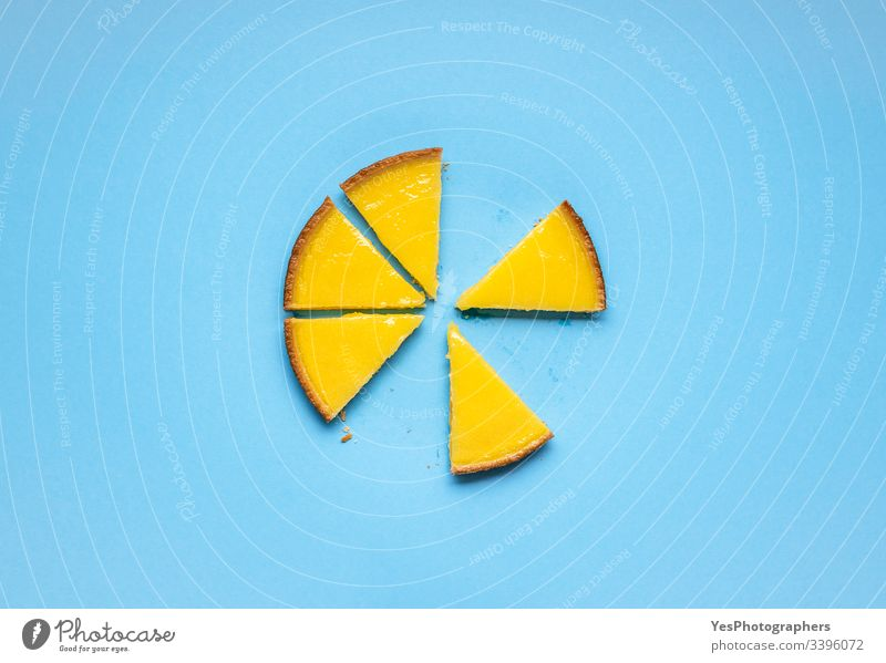 Geschnittener Zitronenkuchen auf blauem Hintergrund. Scheiben Obsttorte obere Ansicht Blauer Hintergrund Zitrusfrüchte-Torte farbenfroh Küche lecker Dessert