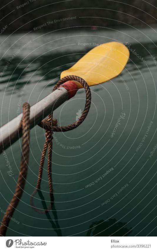 Ein gelbes Paddel, mit einem Seil umwickelt, schwebt über grünem Wasser Kajak Meer Sport rudern Bewegung Außenaufnahme Ferien & Urlaub & Reisen Wassersport