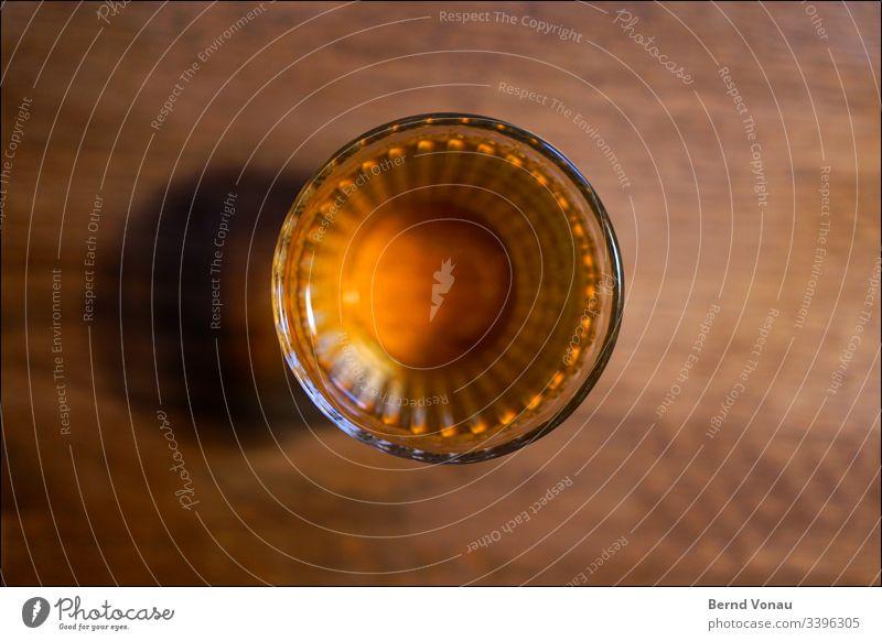 Trinkglas von oben Glas trinken Holztisch unscharf Rand zuhause Getränk Nahaufnahme Flüssigkeit Alkohol Farbfoto gelb Kunstlicht