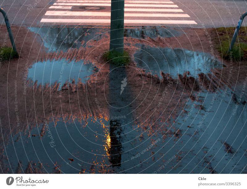 Regenpfützen und Zebrastreifen Fußgängerübergang Straßenbeleuchtung Matsch Regenwetter Schlechtes Wetter Außenaufnahme Laterne schlechtes Wetter Stadt nass