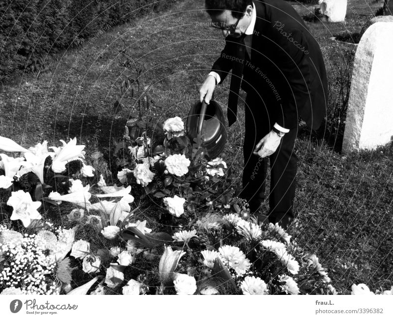 Etwas konnte für den alten Mann noch getan werden, dachte er, und goss die Blumen auf dem frischen Grab. Friedhof Trauer Beerdigung Außenaufnahme Tod