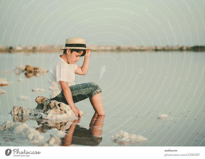 trauriger und nachdenklicher Junge, der am Strand sitzt Kind Kindheit nostalgisch Gedanke Einsamkeit einsam Ausdruck Freiheit Unschuld Porträt ernst träumen
