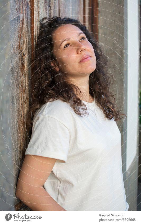 Porträt eines gesunden Mädchens, mit weißer Bluse, mit gelocktem Haar, brünett und nach oben schauend. Frau jung schön Schönheit Mode Starrer Blick krause Haare