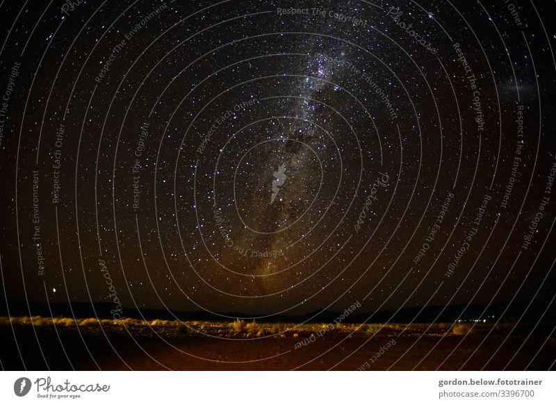 Milchstrasse über Namibia Nachtaufnahme Landschaftsaufnahme wenig Farbe Sternenhimmel scharzer Himmel mit Sterne wenig Vegetation licher in der rechten Bildecke